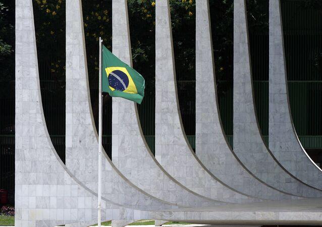 Bandeira do Brasil em frente de colunas do edifício do Supremo Tribunal Federal em Brasília, Brasil (foto de arquivo)