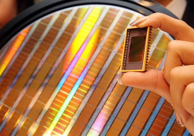 Uma empregada da Samsung Electrinics mostra o primeiro dispositivo de memória de 30 nanômetros e capacidade para 64 gigabits em um evento em Seul em 23 de outubro de 2007