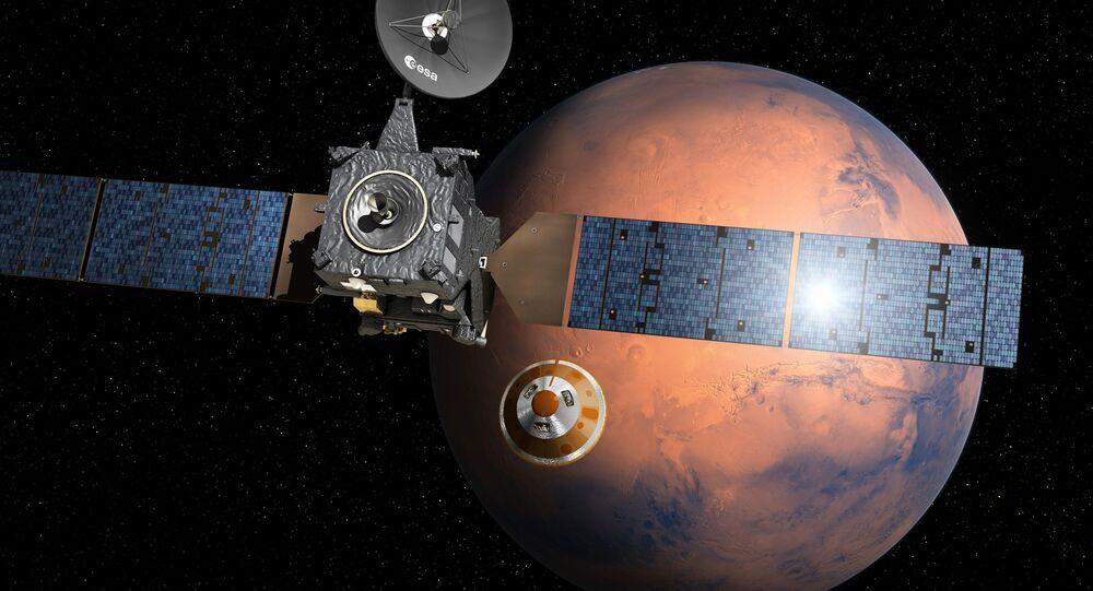 O aparelho Trace Gas Orbiter (TGO) lança a sonda Schiaparelli no âmbito do projeto ExoMars. Representação artística