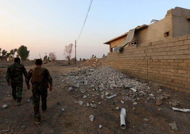 Combatentes de peshmerga passam um edifício destruido no leste de Mossul, Iraque, 26 de outubro de 2016