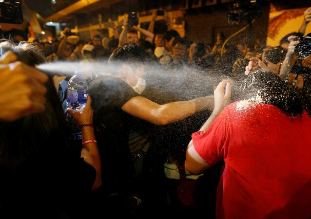 Polícia usando spray de pimenta contra manifestantes durante um protesto contra interferência de Pequim na política local, Hong Kong, China, 6 de novembro de 2016