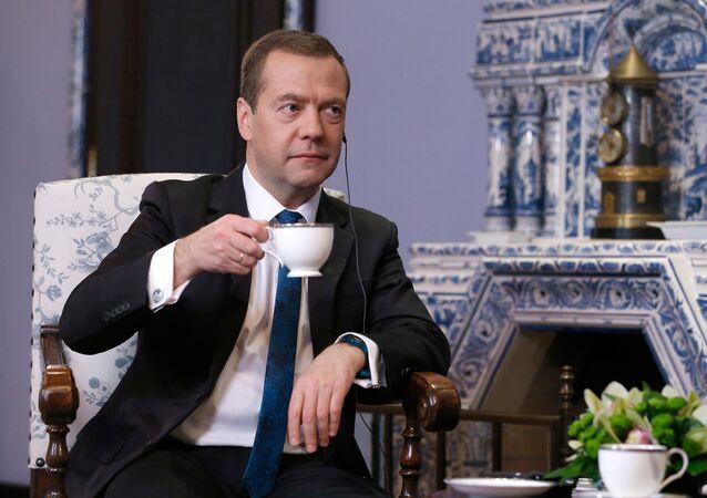 Premiê russo Dmitry Medvedev bebendo café durante uma entrevista ao canal chinês, na sua residência