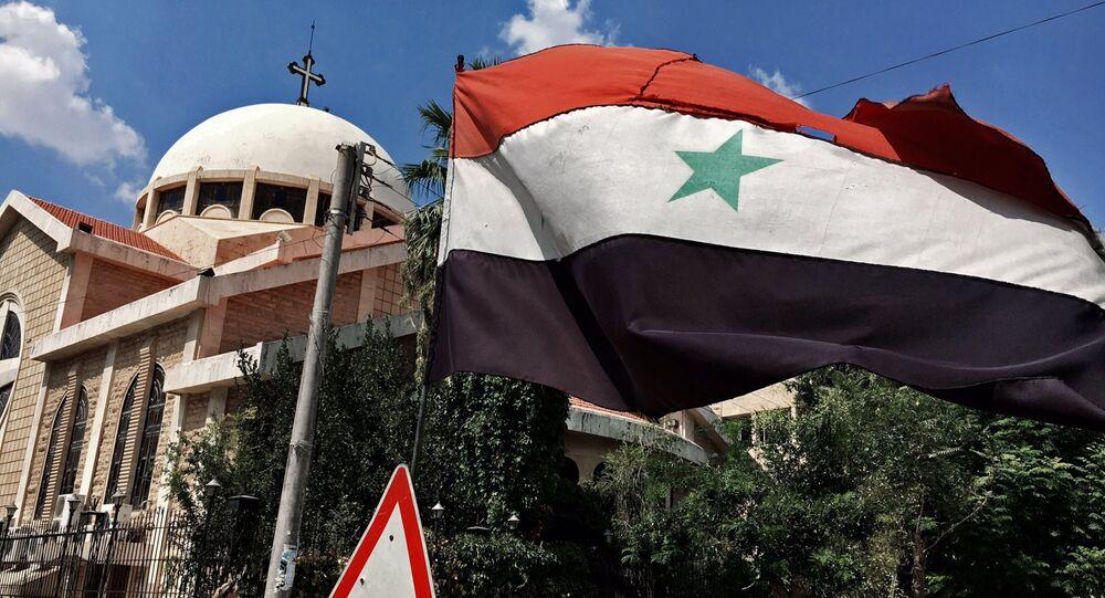 A bandeira do estado da república árabe-síria perto de igreja ortodoxa em um bloco cristão velho de Aleppo, Síria