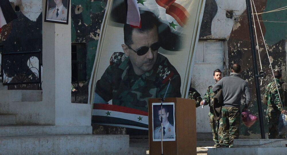 Cartazes com o retrato do presidente sírio, Bashar Assad, junto ao centro de autotreinamento perto de Damasco