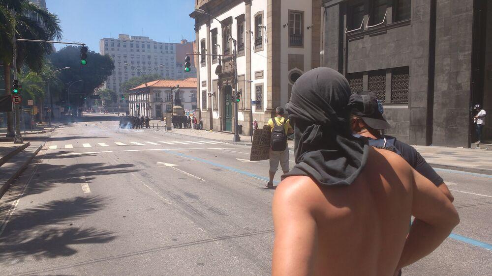 Manifestantes cobrem o rosto em meio a nuvens de gás de pimenta em frente à Alerj - 06/12/2016