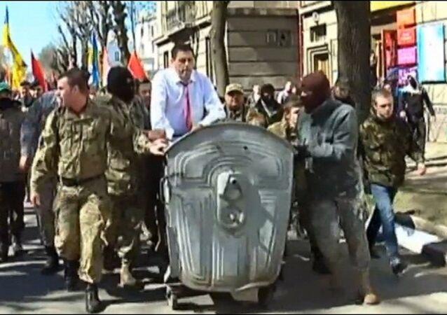 Radicais ucranianos empurrando o chefe do departamento de justiça de Ivano-Frankivsk em uma caçamba de lixo