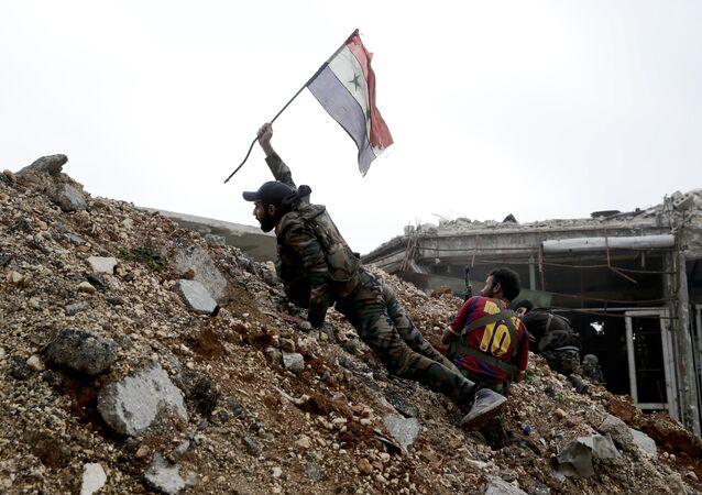Soldado do exército sírio hasteia a bandeira nacional do seu país durante uma batalha com jihadistas em Aleppo, Síria