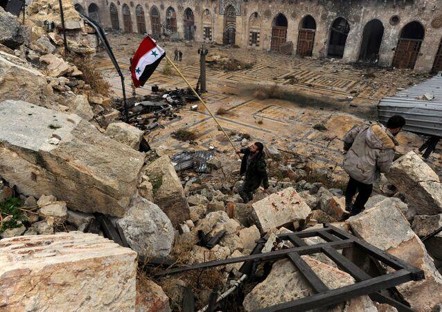 Membro das tropas governamentais hasteia uma bandeira da Síria em Aleppo