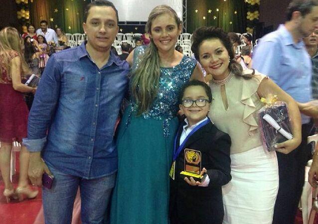 Cadu, o pai, a professora e a mãe na cerimônia do Oscar da Leitura na escola