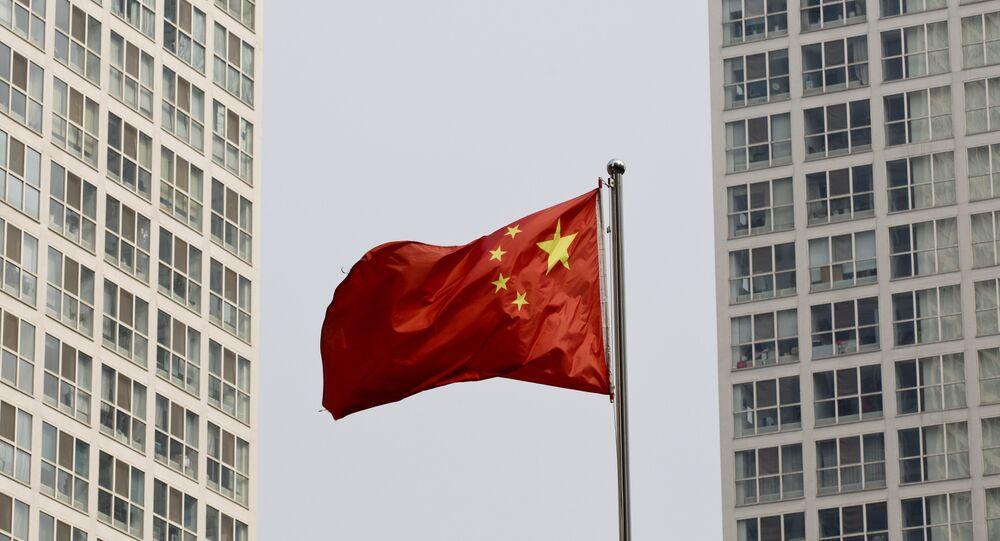 Uma bandeira nacional chinesa vibra no vento entre um complexo residential de grande altura e do escritório em Beijing, China (foto arquiva)