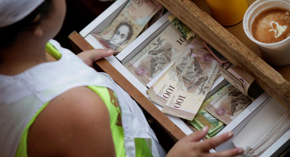 Um caixa recebe notas venezuelanas de bolívar em um mercado no centro de Caracas, Venezuela (arquivo)