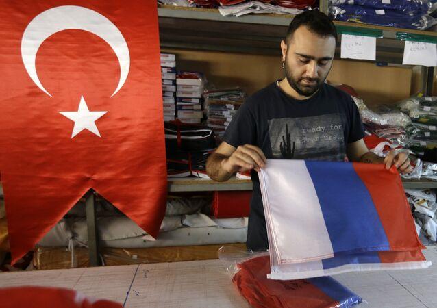 Funcionário de loja manuseia bandeira da Rússia em Istambul, Turquia