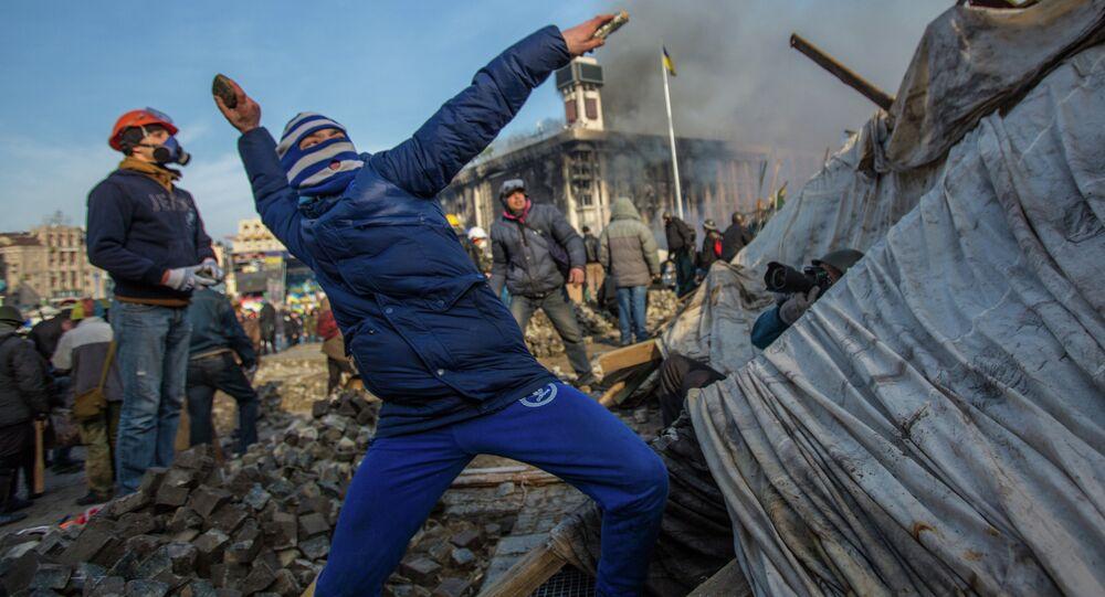 Manifestante jogando pedra na praça Maidan em Kiev, Ucrânia, 19 de fevereiro de 2014