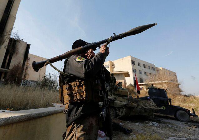 Um membro das Forças de Operações Especiais do Iraque (ISOF) carrega um lançador de foguetes na Universidade de Mossul durante uma batalha contra militantes do Daesh (Estado Islâmico). Mossul, Iraque