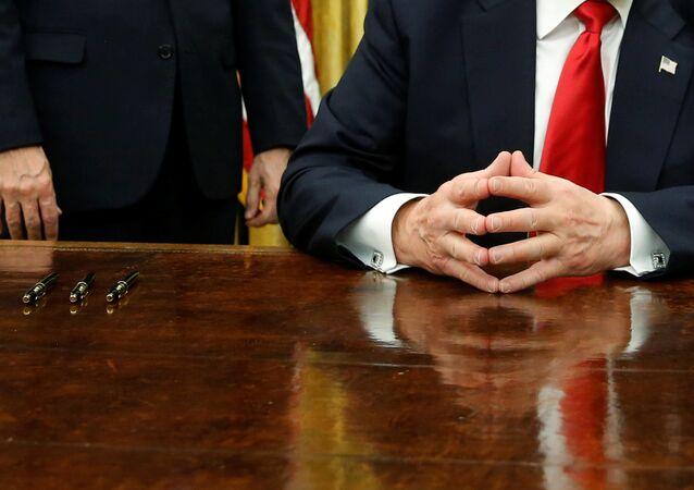 Trump assina primeiros decretos como presidente dos EUA, no Salão Oval, em 20 de janeiro de 2017