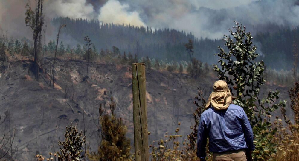 Habitante rural observa um incêndio florestal no Chile.