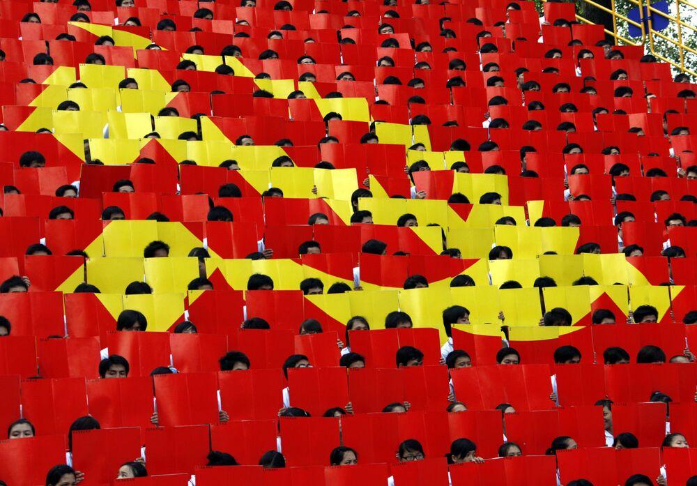 Na cidade de Ho Chi Minh, estudantes seguram cartões formando a bandeira do Partido Comunista do Vietnã.