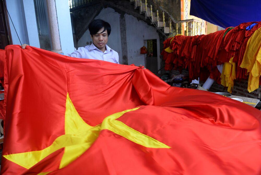 Trabalhador da oficina vietnamita segura bandeira nacional na véspera do Ano-novo chinês.