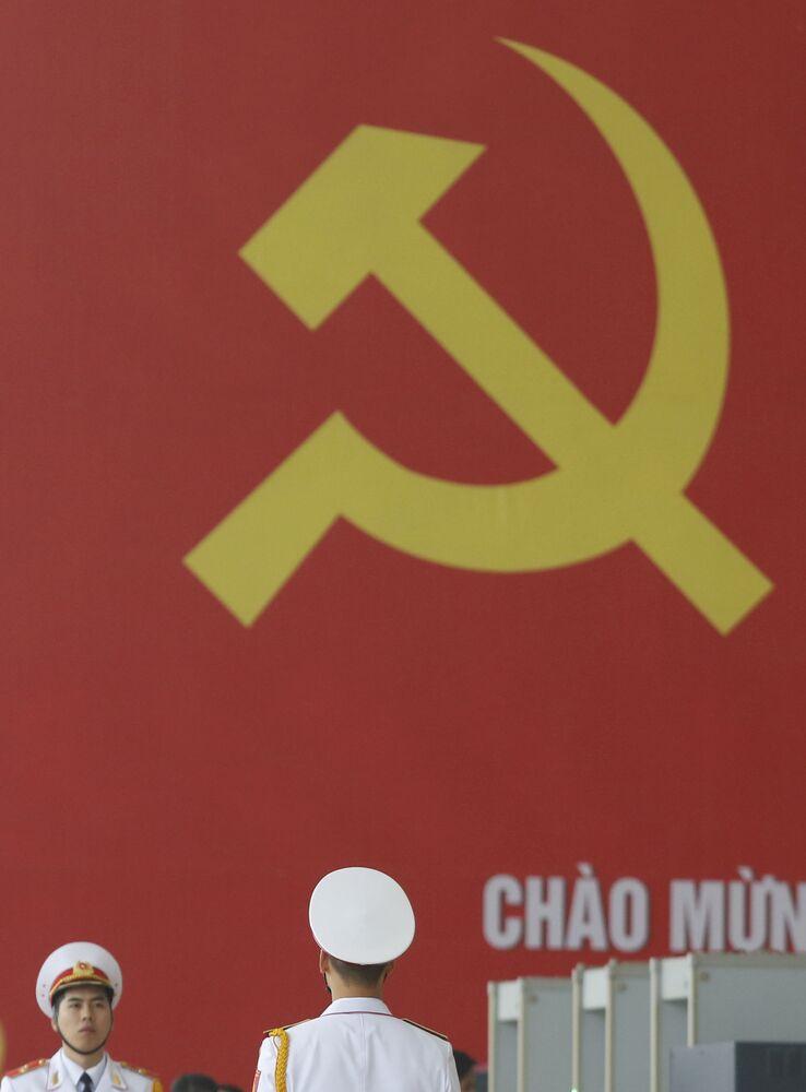 Militares estão servindo com a bandeira do Partido Comunista do Vietnã no fundo, celebrando seu 12º Congresso Nacional em Hanói.
