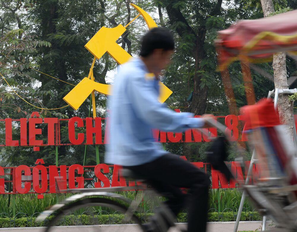 Velocipedista na Rua de Hanói passa pelo símbolo que marca o 87º aniversário do partido governante vietnamita que se dá em 3 de fevereiro de 2017.