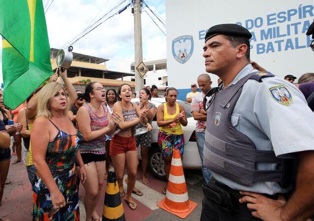 Um agente guarda a entrada da sede da PM em Cachoeira do Itapemirim, ES, enquanto moradores protestam contra a greve policial, que levou ao caos no estado, em 7 de fevereiro de 2017