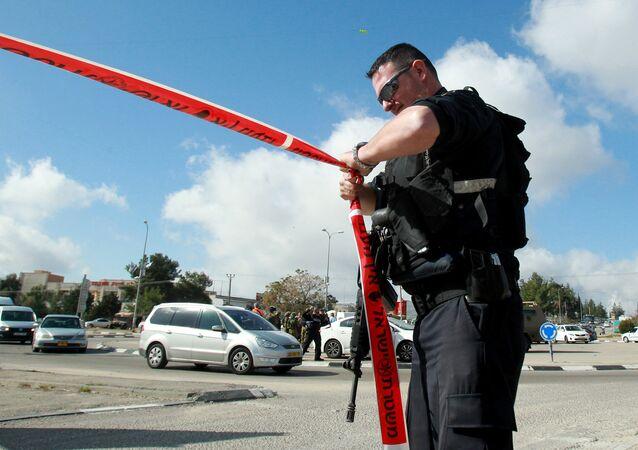 Um agente das forças de segurança israelenses isolando um perímetro com uma fita policial