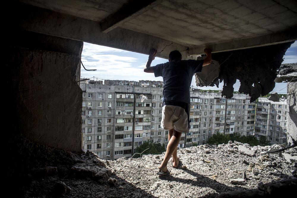 Foto da série Dias Negros da Ucrânia de Valery Melnikov, na qual aparece um homem que avalia a destruição de um prédio atingido por ataque de artilharia em Lugansk