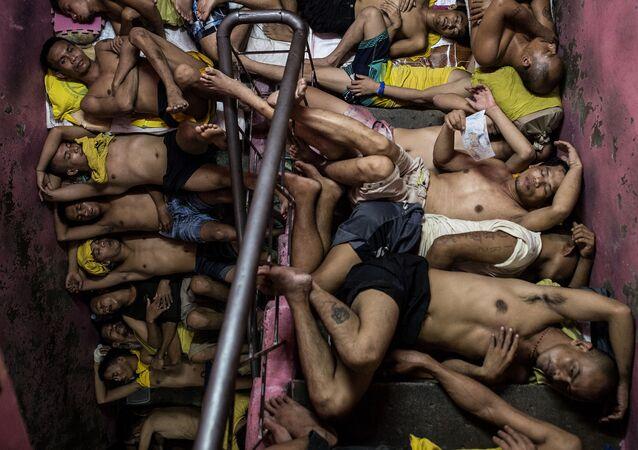 Foto da série Vida Dentro da Prisão Mais Superlotada das Filipinas, de Noel Celis, que mostra dezenas de prisioneiros dormindo nos degraus da escada da prisão Quezon City em Manila