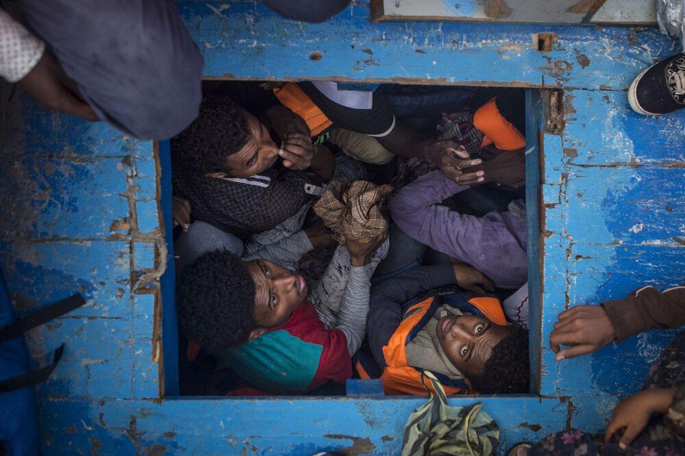 Imagem da série Migração Mediterrânea de Mathieu Willcocks que retrata migrantes eritreus apinhados no porão de um barco de madeira que transportou cerca de 540 homens, mulheres e crianças