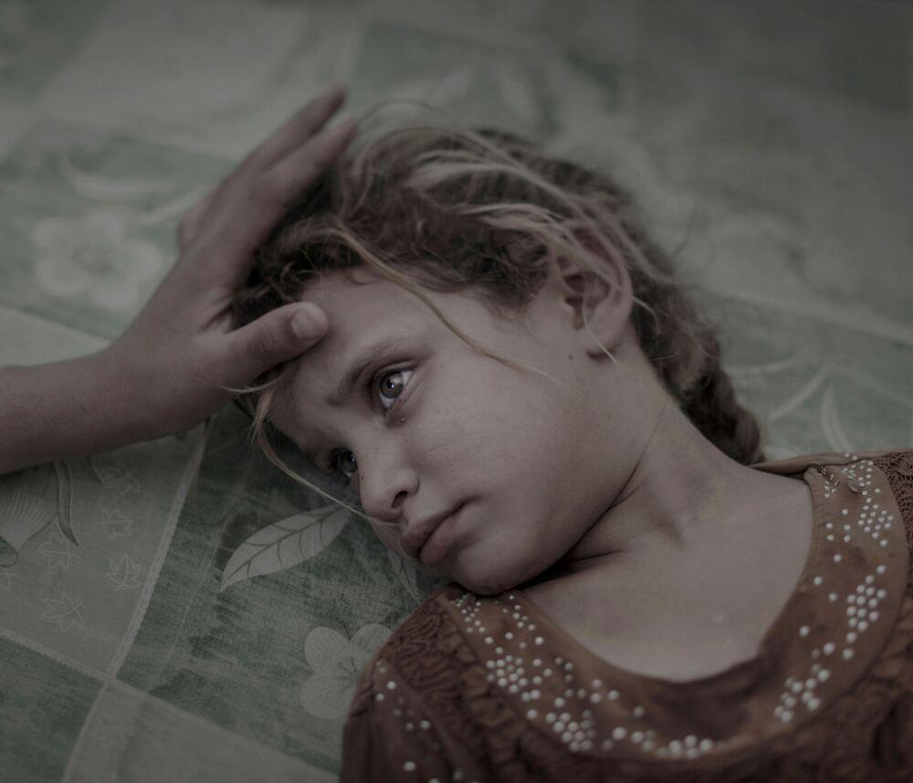 Foto chamada O que Daesh Deixou, do fotógrafo Magnus Wennman, retrata a menina iraquiana Maha deitada no chão de um campo de refugiados sobrelotado