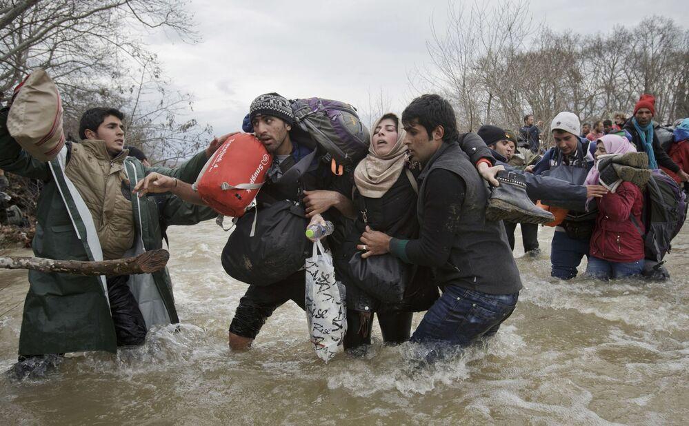 Imagem batizada como Passada de Migrantes, de Vadim Ghirda, retrata uma mulher apoiada por dois homens atravessando um rio em tentativa de atingir a Macedônia