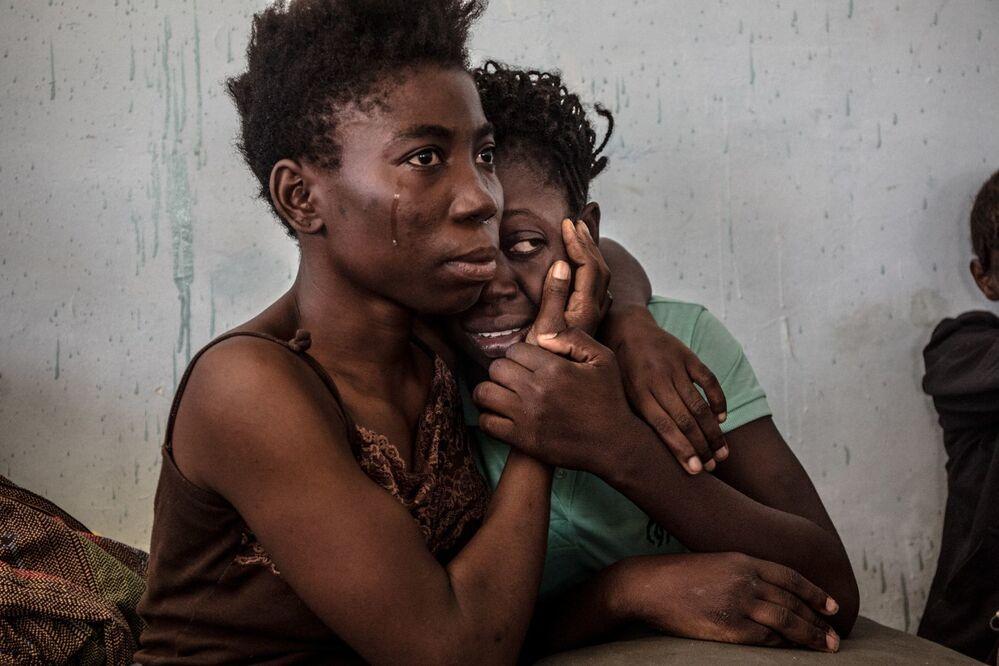 Foto denominada como Armadilha Migratória Líbia retrata dois refugiados nigerianos chorando e se abraçando no centro de detenção para refugiados conhecido por acusações de assalto sexual e violência, em Surman, na Líbia