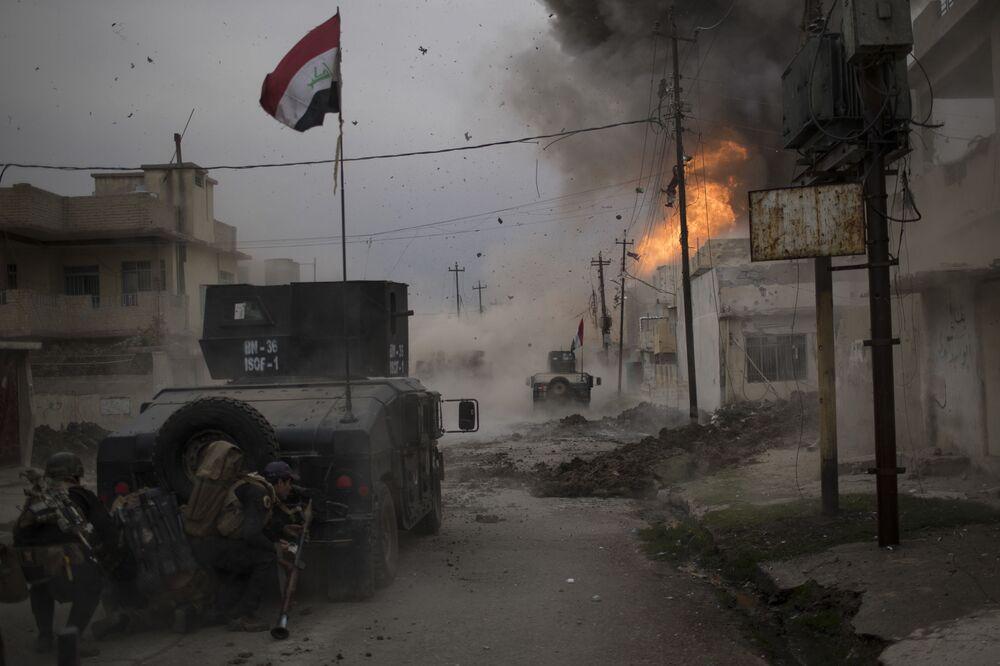 Imagem denominada como Batalha por Mossul, do fotógrafo Felipe Dana, mostra um carro-bomba explodindo junto a veículos blindados das forças especiais iraquianas no caminho para Mossul, cidade iraquiana controlada pelo Daesh