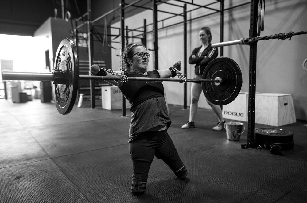 Imagem da série Atleta Adaptável, de Darren Calabrese, que mostra a lutadora Lindsay treinando com ajuda de correntes e fitas para levantamento terra sob olho vigilante da sua técnica Jenny Jeffries