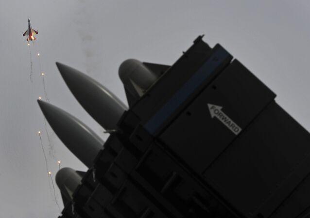 Mísseis Spyder superfície-ar em uma exposição estática são observados enquanto um jato F-16 da esquadrilha acrobática da Força Aérea de Singapura, Cavaleiros Negros, lança foguetes luminosos no quarto dia do Singapore Air Show em Singapura, na sexta-feira, 14 de fevereiro de 2014