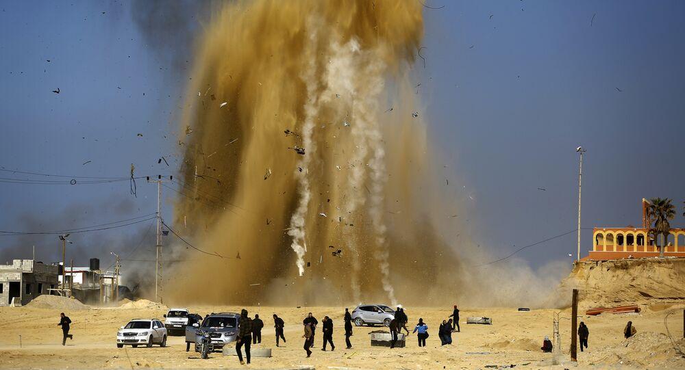 Palestinos fugindo para se protegerem, enquanto a fumaça sobe após um ataque aéreo de Israel a um posto do Hamas, Faixa de Gaza (foto de arquivo)