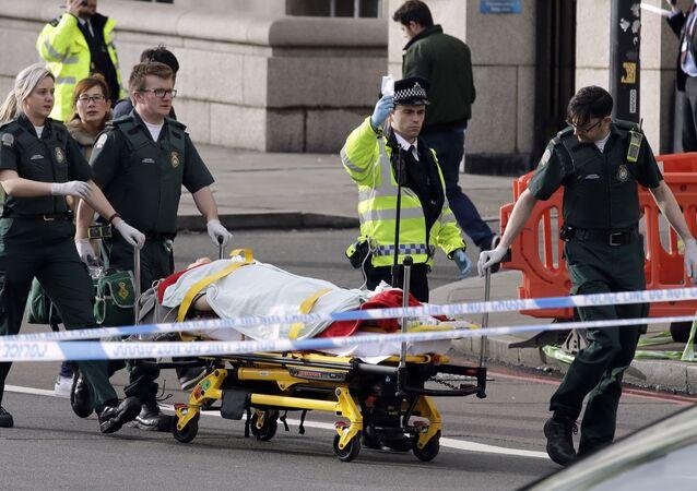 Polícia e médicos levam para a ambulância uma pessoa ferida
