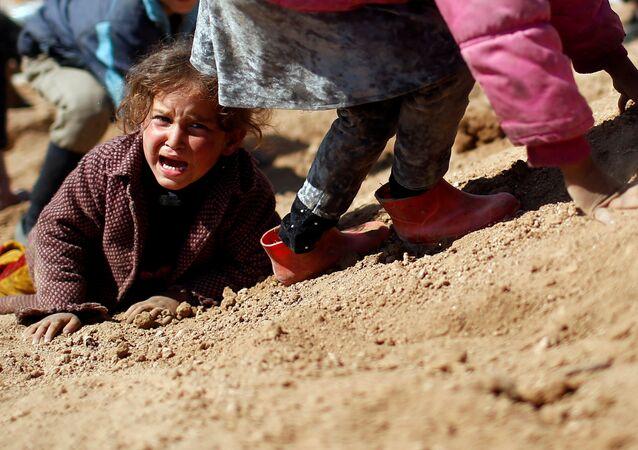 Criança iraquiana chora ao entrar no campo de refugiados Hamam al-Alil, enquanto as forças do Iraque lutam contra os terroristas do Daesh, Iraque, março de 2017