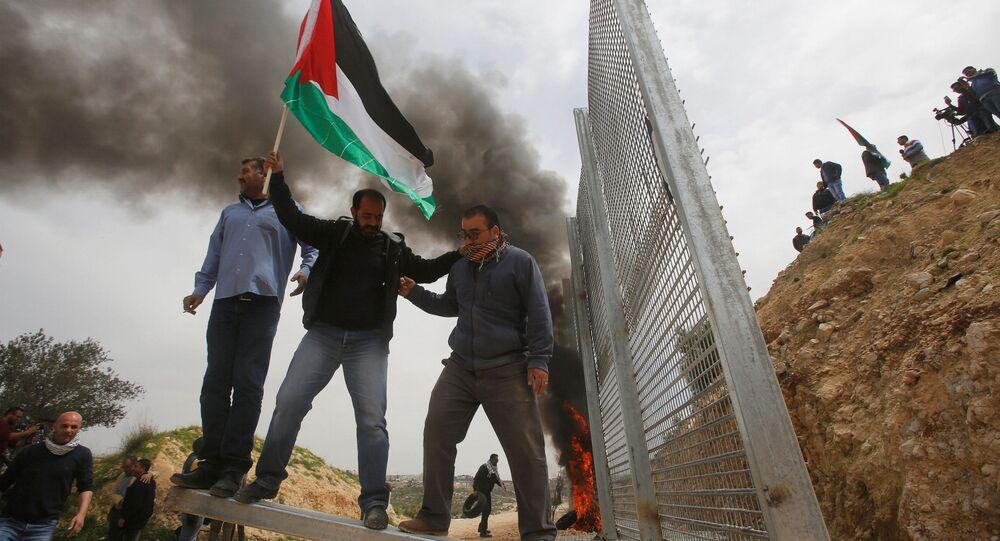 Palestinos tentam remover parte da cerca israelense durante um protesto na Cisjordânia, em 30 de março