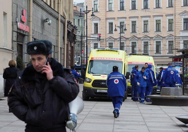 Um agente da polícia russa fala pelo telefone enquanto um grupo de médicos forenses auxiliam pessoas feridas na entrada da estação Tekhnologichesky Institut do metrô de São Petersburgo, onde uma explosão matou pelo menos 9 pessoas em 3 de abril de 2017