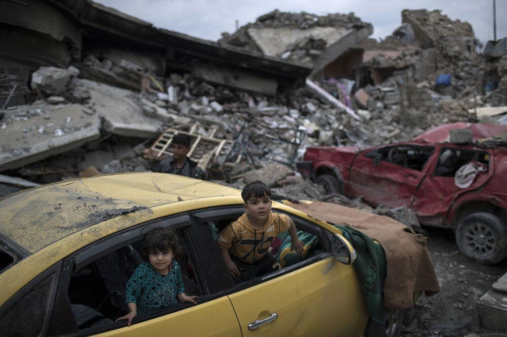 Meninos em carro danificado na parte ocidental de Mossul
