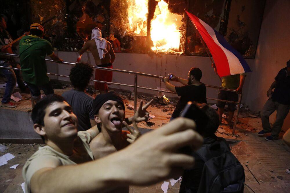 Homens tiram selfie com prédio do Congresso no fundo, durante confrontos com a polícia no Paraguai