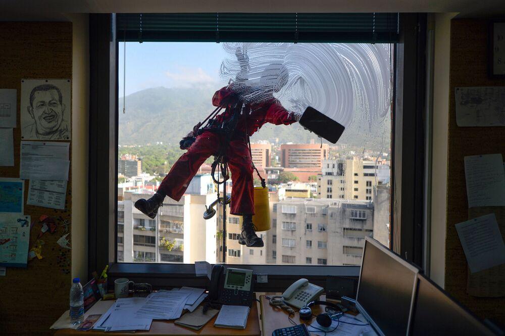 Lavador de janelas em um dos prédios da capital venezuelana, Caracas
