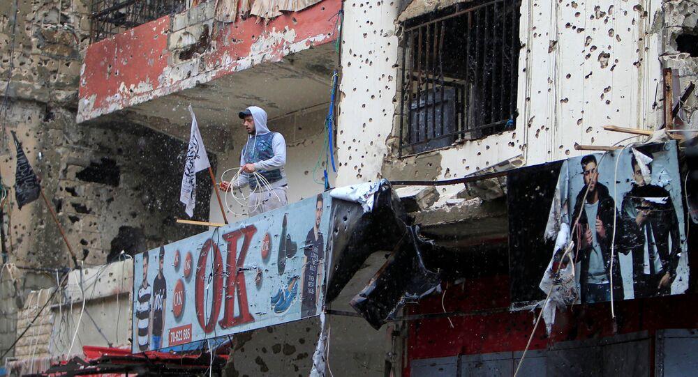 Homem na varanda de um dos edifícios com marcas de bombardeios em um campo de refugiados na Líbia