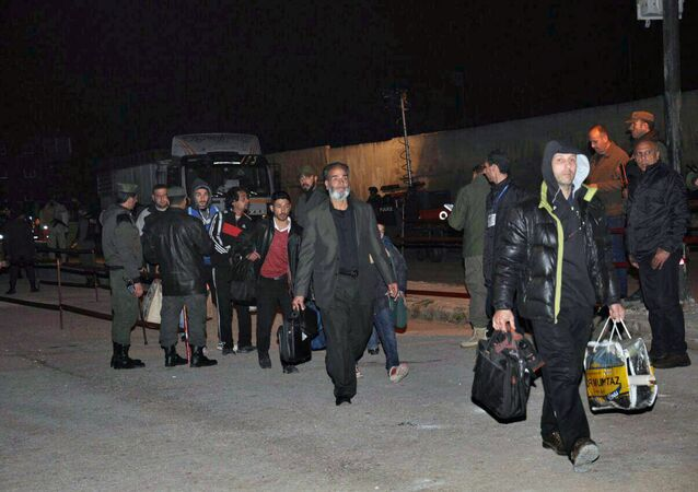 Militantes, que lutam contra o governo sírio, rumo a um ônibus para deixar o bairro Al Waer em Homs (foto de arquivo)