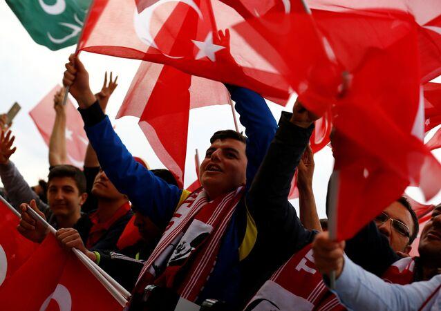 Os apoiantes do presidente turco, Recep Tayyip Erdogan, agitam bandeiras nacionais enquanto aguardam sua chegada ao Palácio Presidencial em Ancara, Turquia, após a realização do referendo que lhe concedeu novos poderes e mudou o regime de parlamentarista para presidencialista.