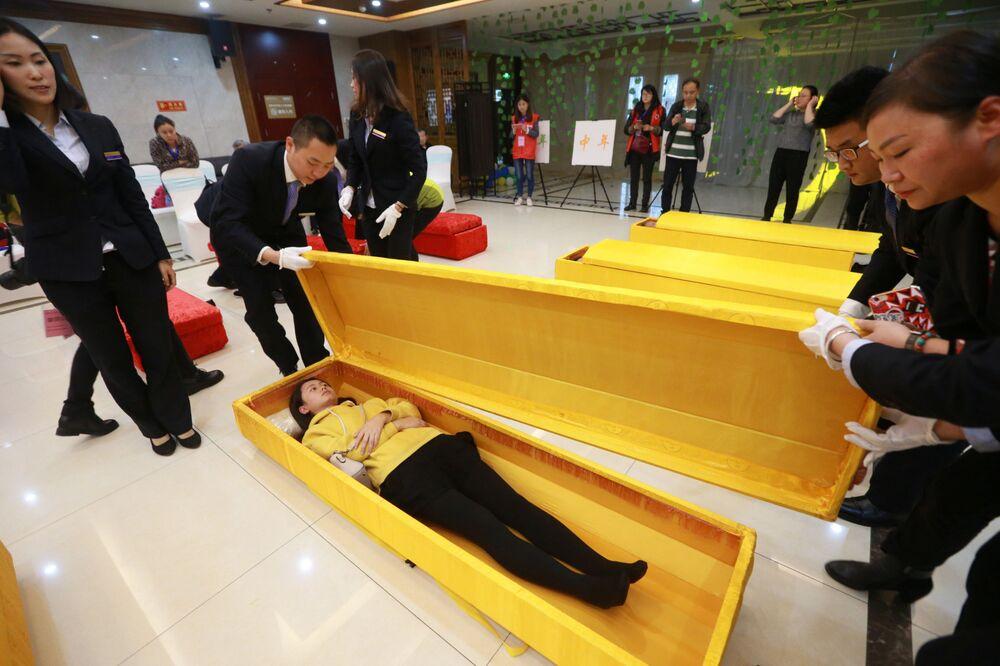 Cliente experimenta caixão durante abertura de uma nova funerária em Chongqing, China