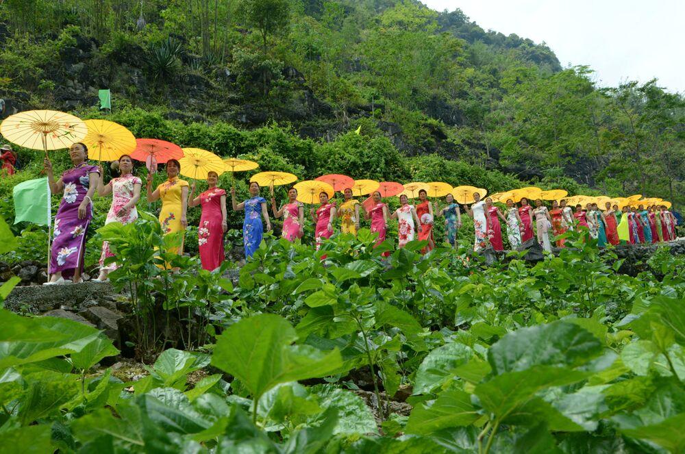 Mulheres exibem trajes tradicionais da China em meio a uma plantação em Laibin, em Guangxi