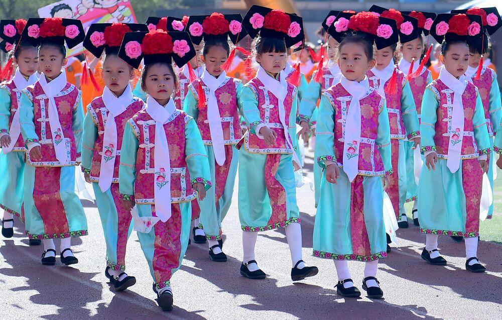Pequenos estudantes desfilam com roupas tradicionais chinesas durante evento esportivo em Shenyang