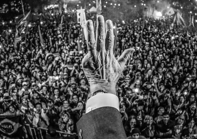 Mão do presidente Lula acenando para a multidão durante ato em Curitiba, no Paraná